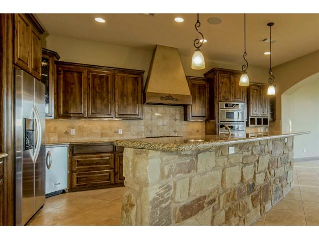 Cooks delight kitchen with sandstone bar surround, knotty alder