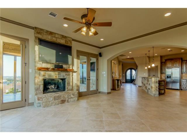 Open family room off the kitchen with sandstone fireplace, custo