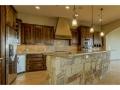 Cooks delight kitchen with sandstone bar surround, knotty alder